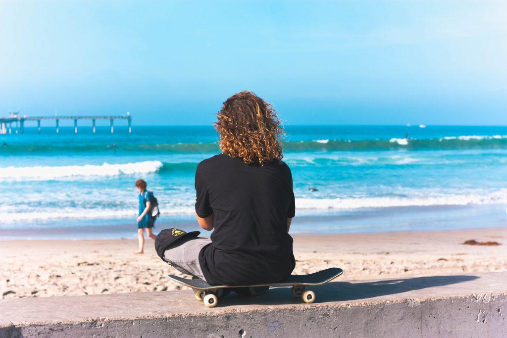 sahilde kaykay üzerinde oturan biri