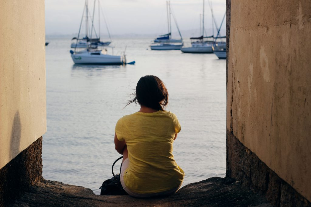 woman sitting by the water, pensive and thoughtful