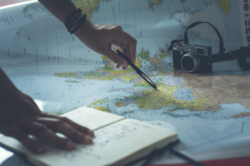 picture of someone pointing to a map with their pen planning a trip