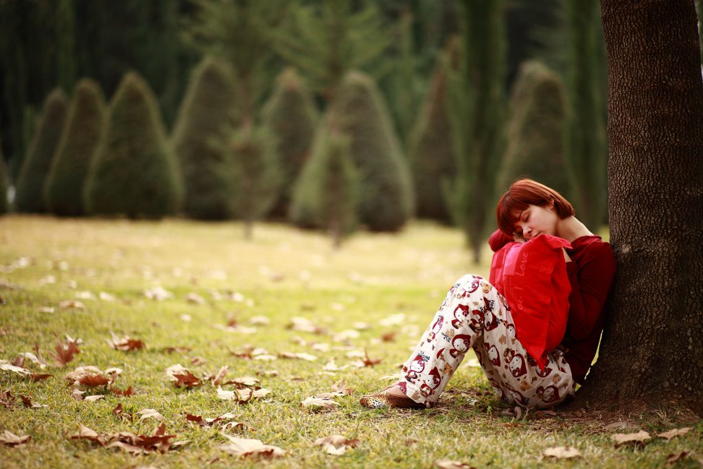 ağaca yaslanarak oturan kadın