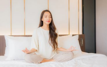 portrait-beautiful-young-asian-woman-meditation-bed-bedroom-interior (1)