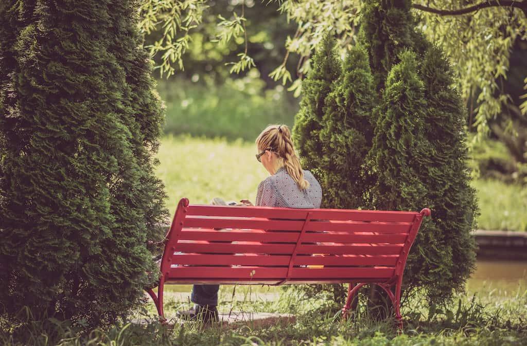 женщина сидит на берегу и читает книгу