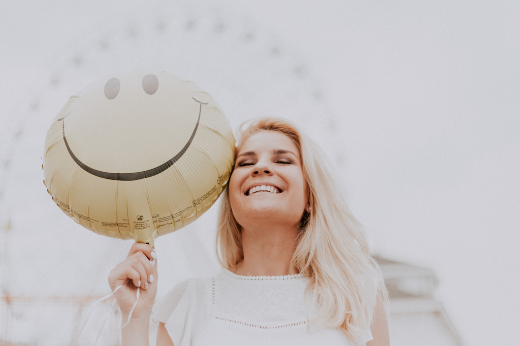 woman, smiles with a smiley baloon