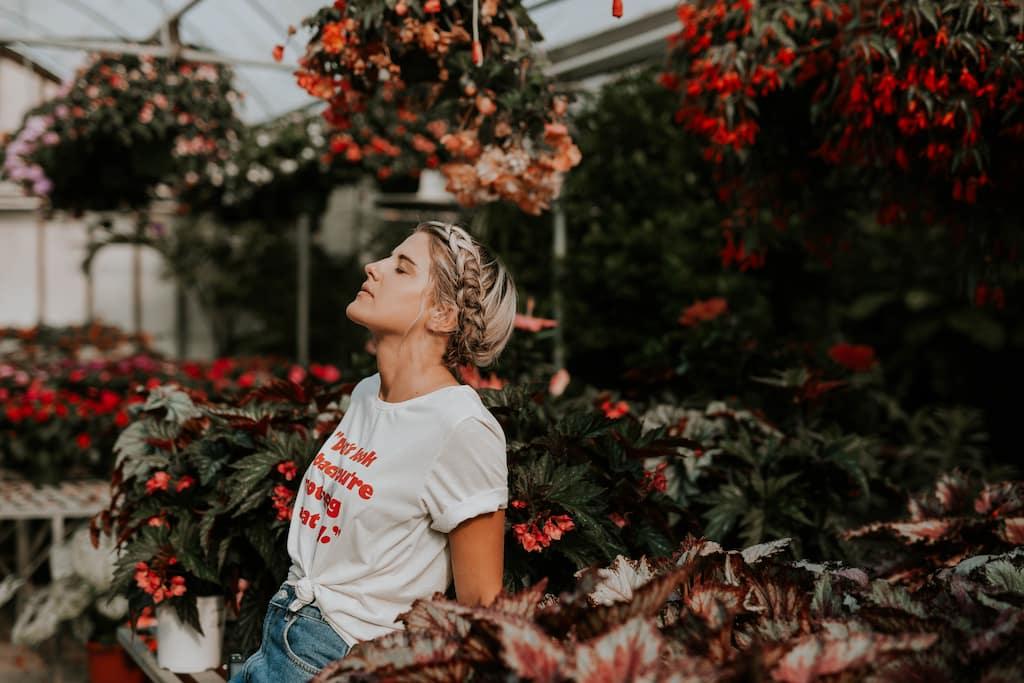 çiçekler arasında nefes alan kadın