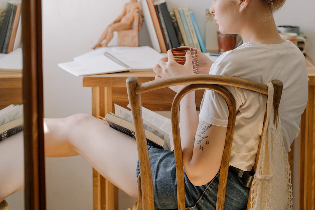 thoughtful woman sitting in her room while holding a coffee