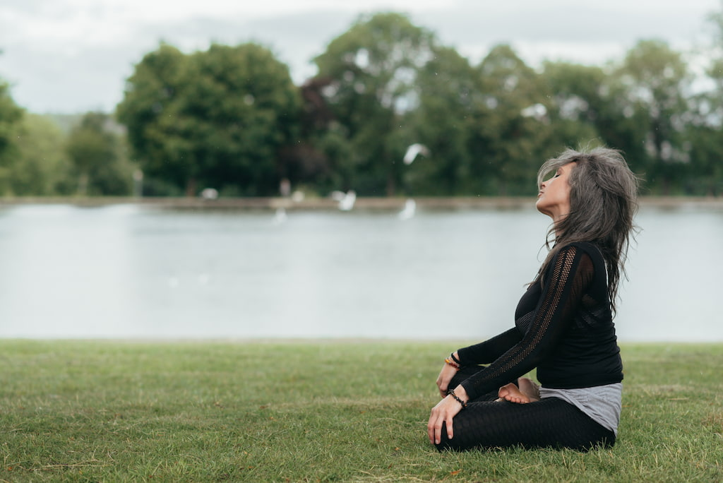 woman is meditating by the sea
